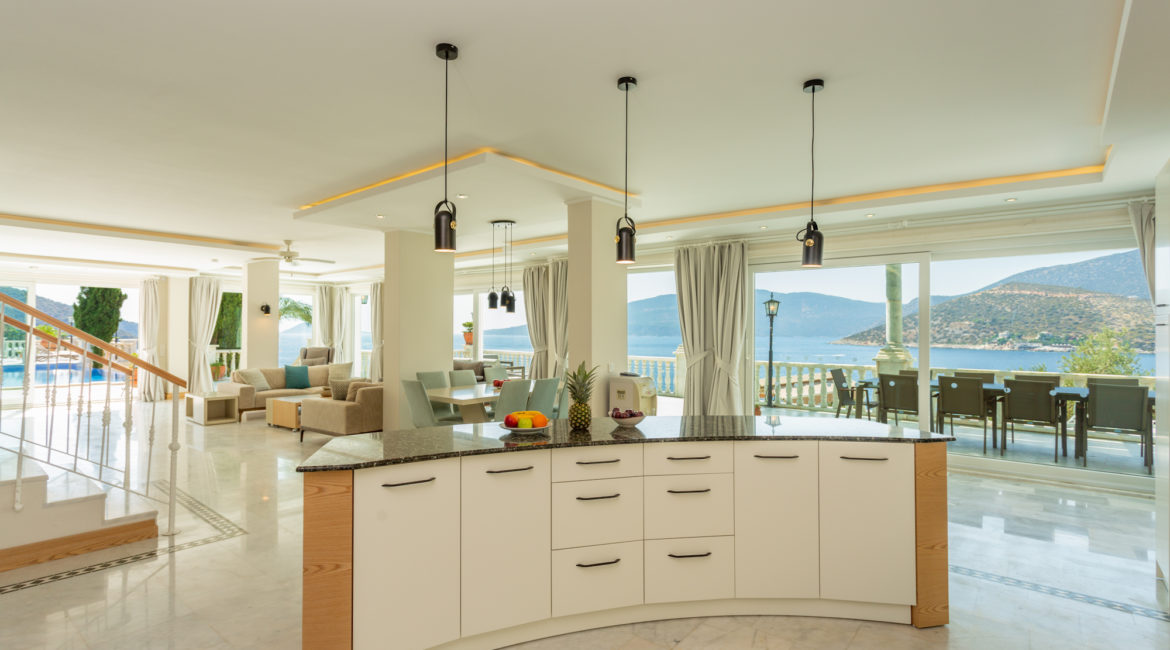 Open plan kitchen, dining and living area of Mavi Koy and views out across the bay